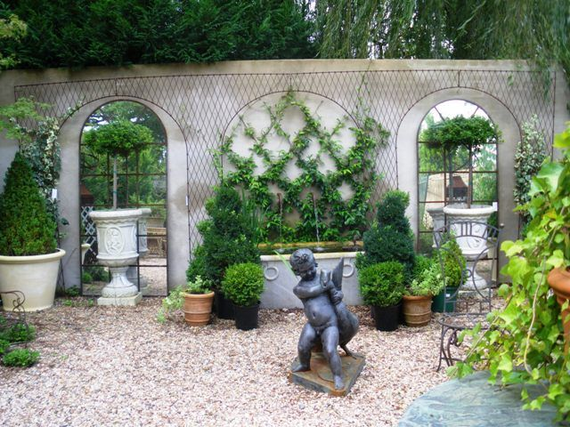 Potted shaped topiaries and latticed ivy are so inviting for French courtyard garden ideas