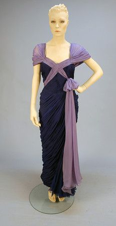 JEAN DESSES CRINKLED CHIFFON EVENING GOWN, MID 20th C. Sleeveless ruched and pleated blue sheath, the back having ruched lavender smooth chiffon forming either wide shoulder or fanning into a capelet, crossing the bodice front and flowing to hem on the left side, draped skirt having a flounced gore to one side, side zipper, taffeta lining. Label: Jean Desses 17. Avenue Matignon. Paris. Front