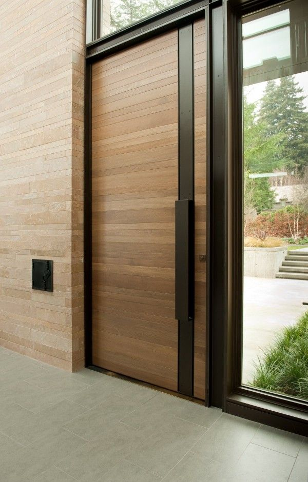 Smooth Horizontal Wood Panels Gain A Contemporary Update With Silky Black Handle Guard That Runs From Top To Bottom Captivating Wooden Door Design