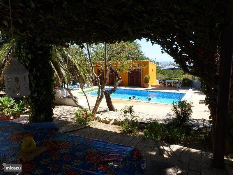 Buiten eettafel onder pergola met uitzicht op zwembad en oceaan