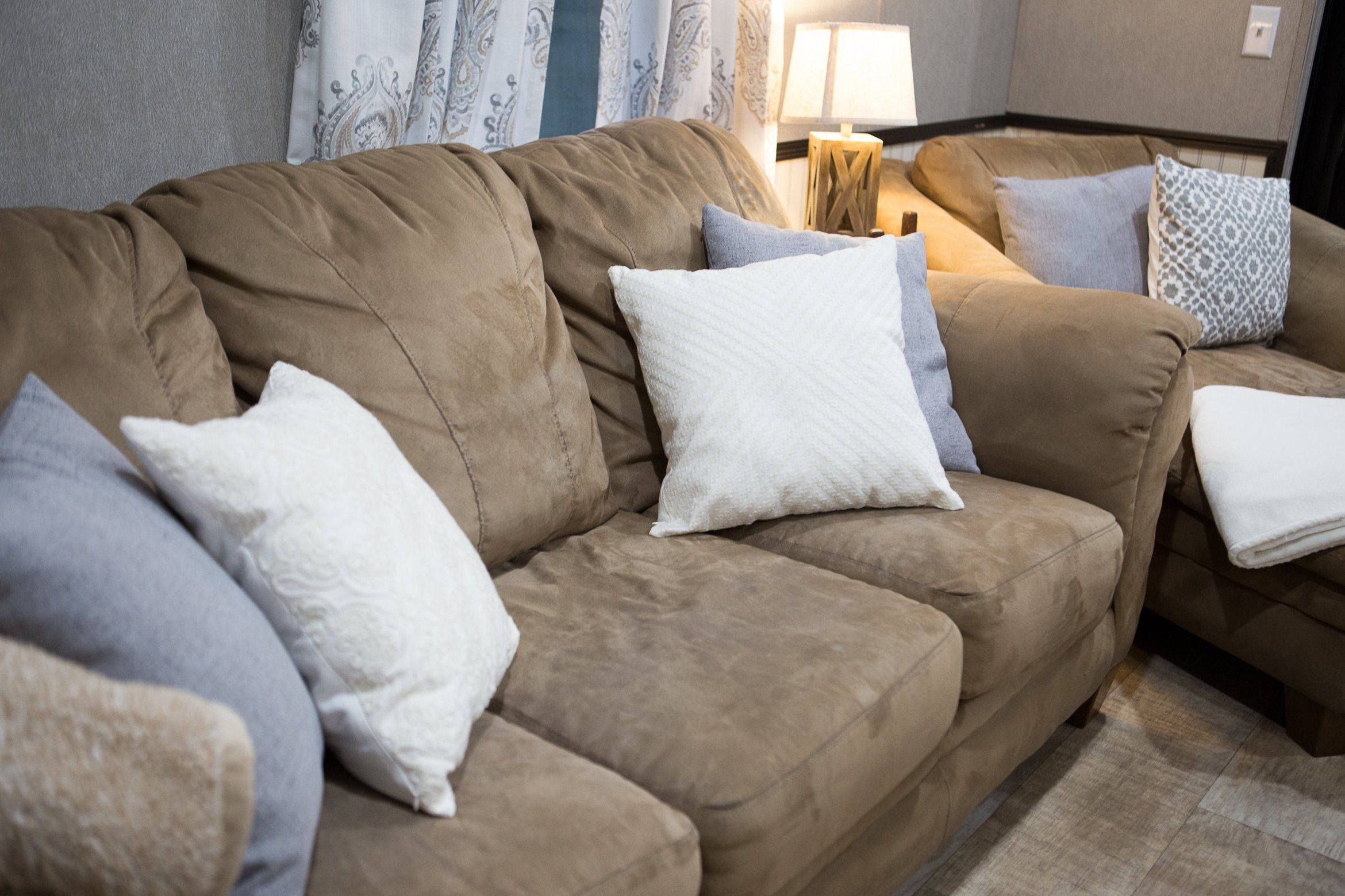 Brown Suede Couch With Grey And White Pillows Decorative Lamp