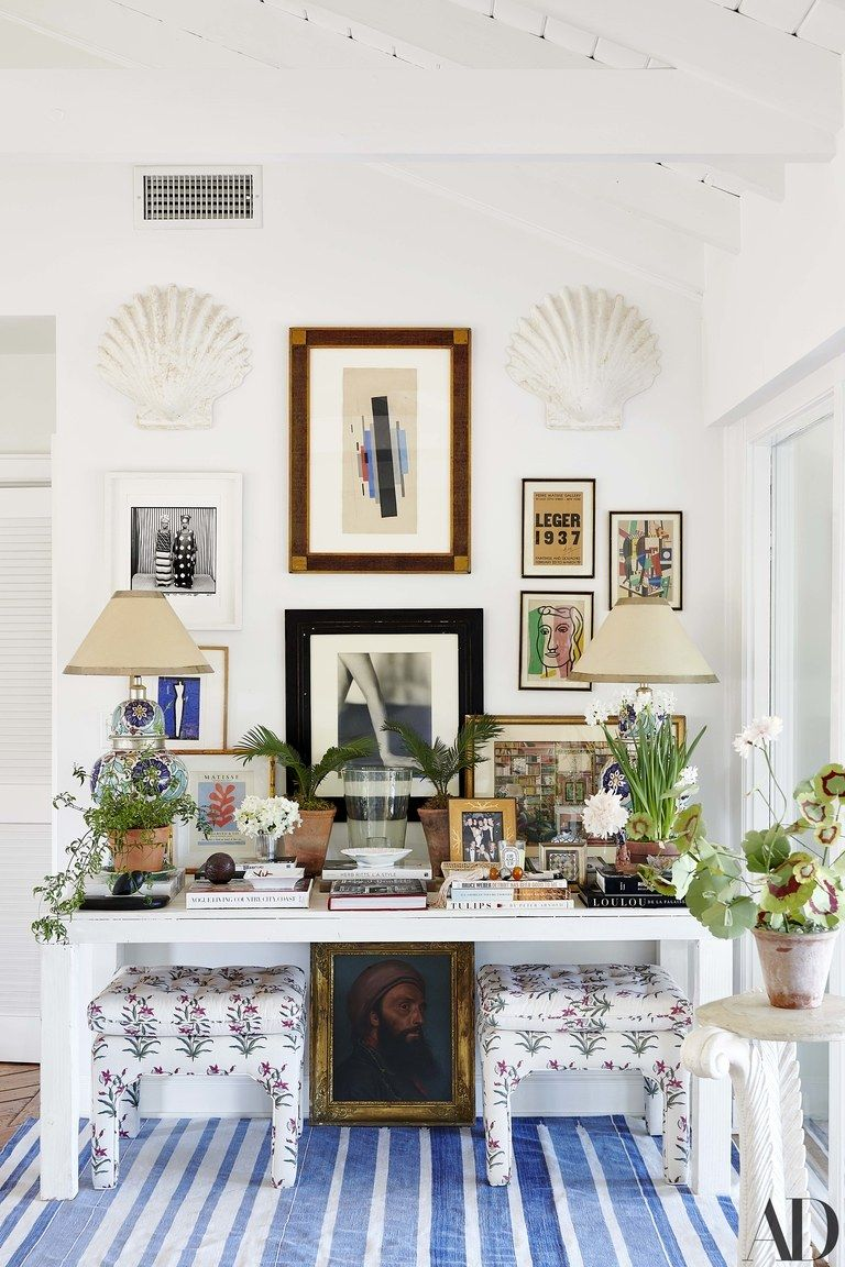 Artworks by Ilia Tchachnik Malick Sidib and Fernand Lger hang above a custom table the Palm Beach Regency stools are...