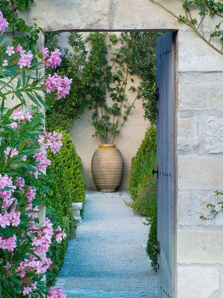 puerta de madera y marco de piedra para acceder al jardn