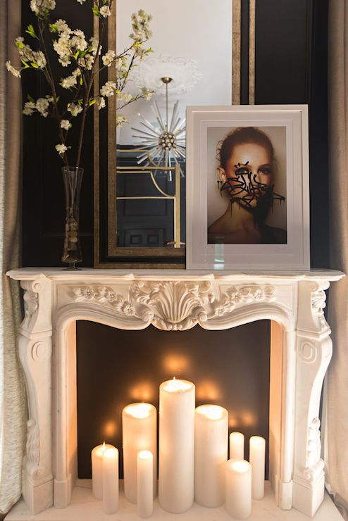 Master bedroom fireplace features an ornate carved marble fireplace mantel  filled with lit candles and topped - Master Bedroom Fireplace Features An Ornate Carved Marble
