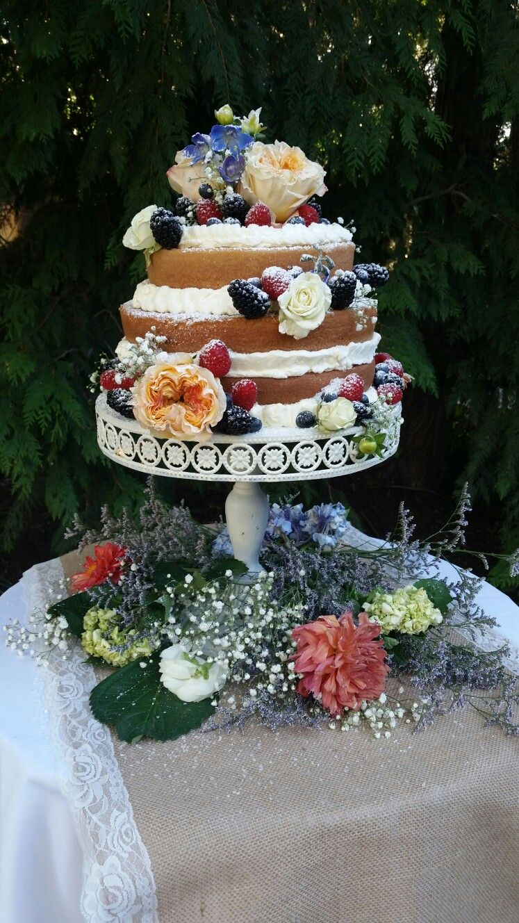 Exposed layered wedding cake with fruit and flowers