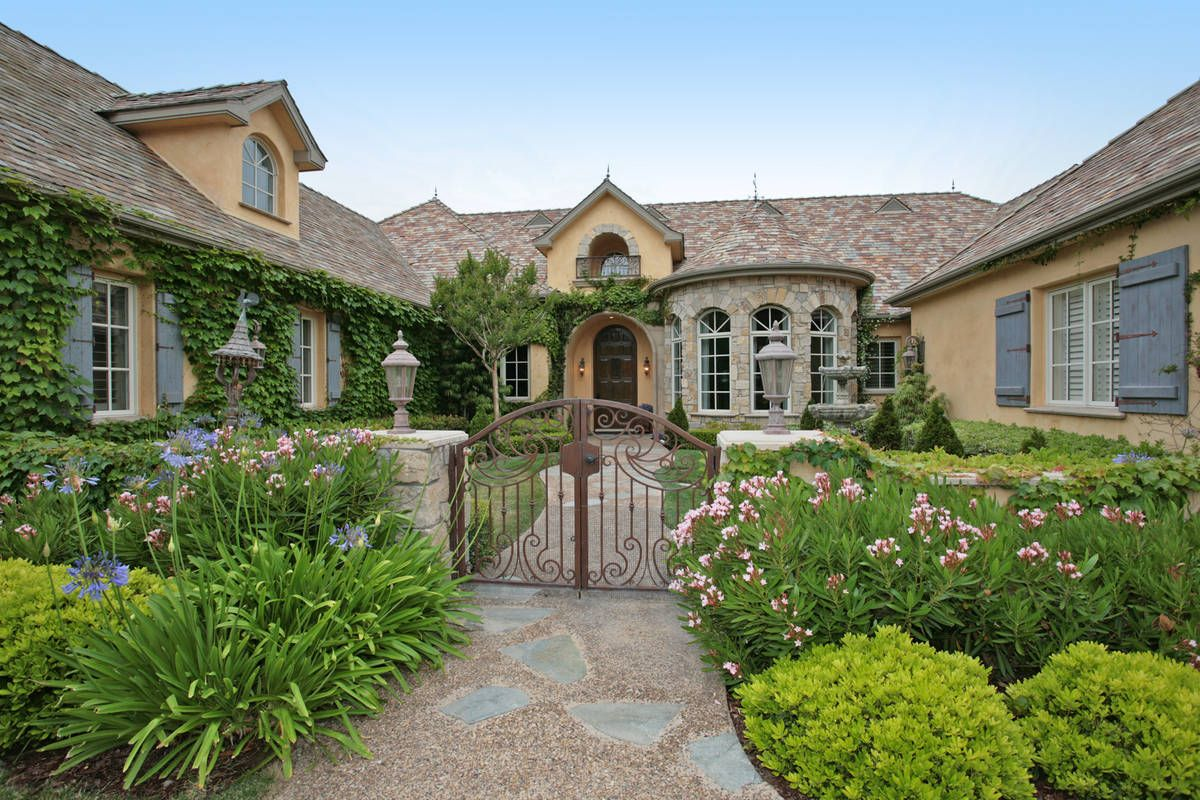 French Country house with iron gate, stone walkway and ivy growing ...