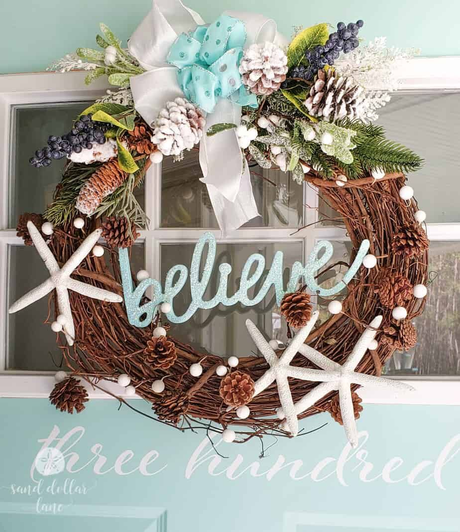 This fun Coastal Christmas wreath on the front door is like a little sneak peek at the coastal Christmas decor that's going on inside the house! #coastalchristmas #christmasdecor #christmasdecorating #christmasdecorations #beachhouse #coastalliving #holidaydecor #christmaswreath #coastalwreath