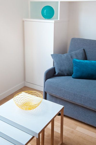 Tables gigognes blanches Kilo (Habitat) pour permettre le débattement du canapé-lit et coupe jaune en métal Monoprix. Coussin turquoise chez Graine d'Intérieur, et boule lampe turquois chez Habitat.