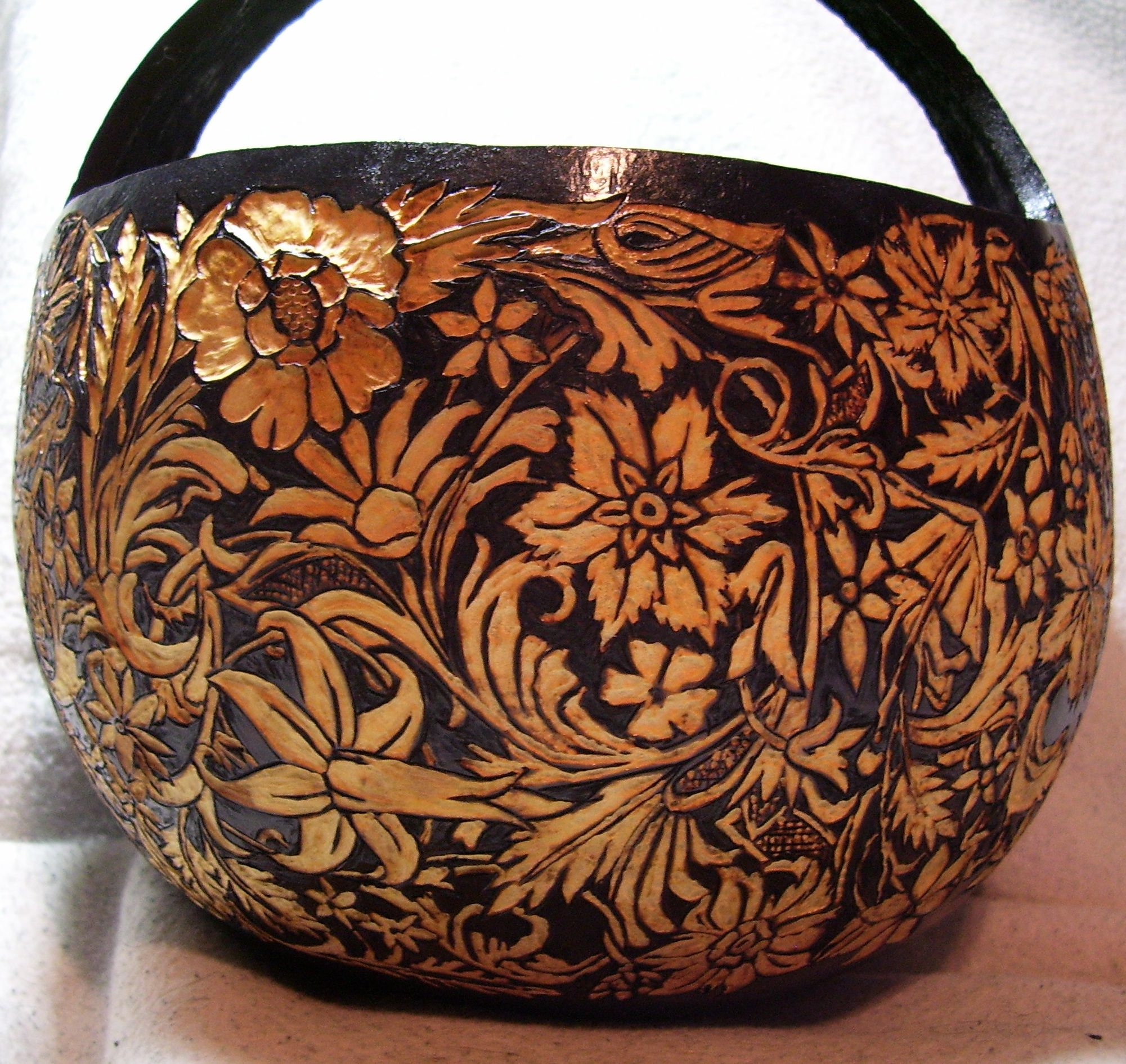 A carved gourd basket in leather tooling patterns