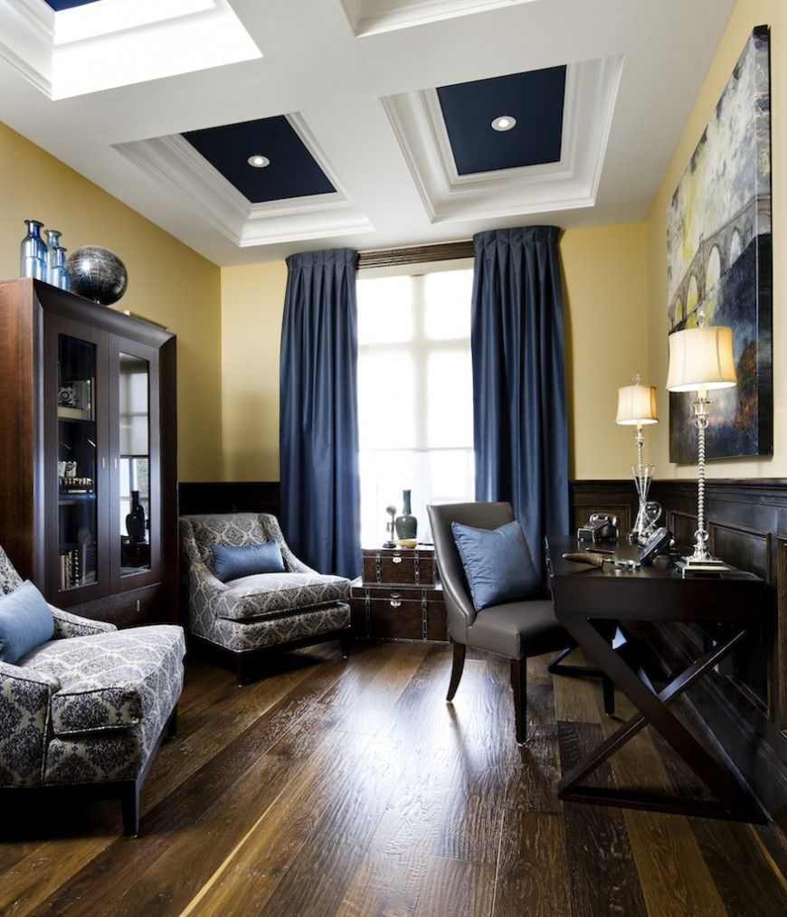 The home office has hardwood floors in varying shades that complements the dark furniture the pale yellow walls are offset by the rich blue curtains and