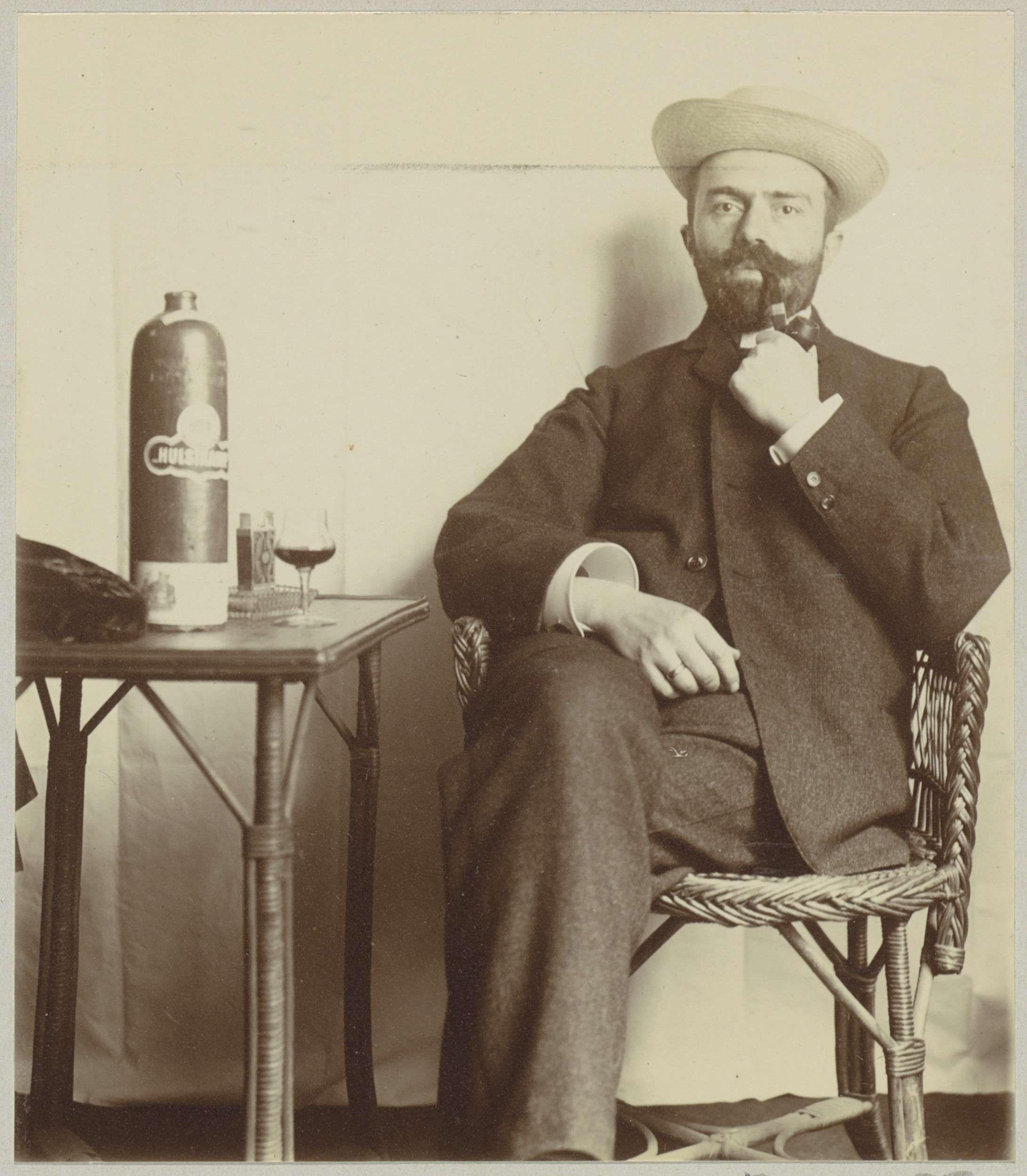Anonymous | Man met hoed, pijprokend bij een kruik drank, Anonymous, c. 1900 - c. 1910 | Onderdeel van Familiealbum met onder meer foto's van Wijnhandel Kraaij & Co. Bordeaux-Amsterdam.