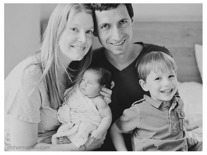 Lifestyle family portrait with newborn indoors on bed