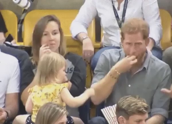 Toddler steals popcorn from Prince Harry