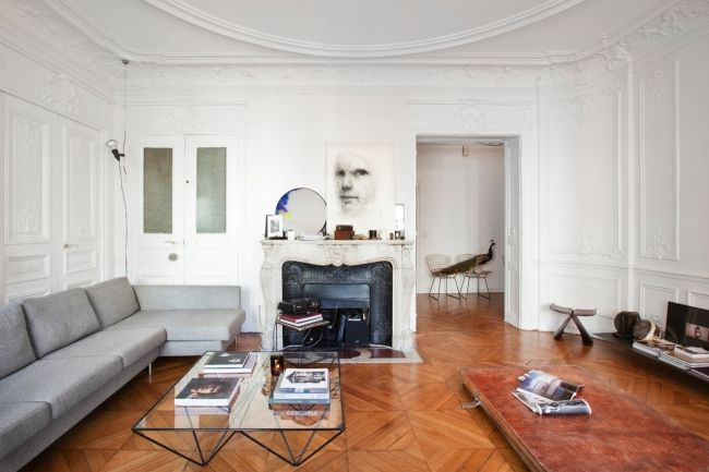 House tour: a pared-back 19th-century apartment in Paris : In the the living room, a 1980s sofa purchased on eBay faces an 'Alanda' coffee table by Paolo Piva for B&B Italia. In the foreground is a pair of vintage leather gym mats repurposed  as a divan.