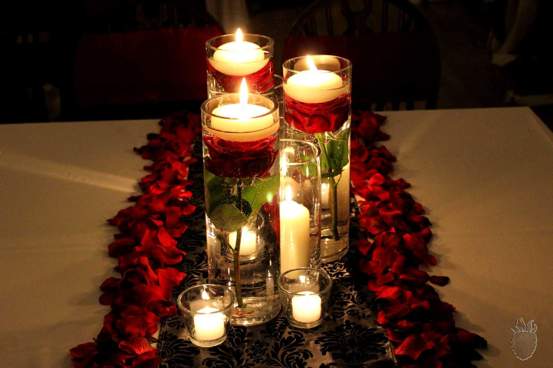 Roses in cylinder vases with candles and rose petals