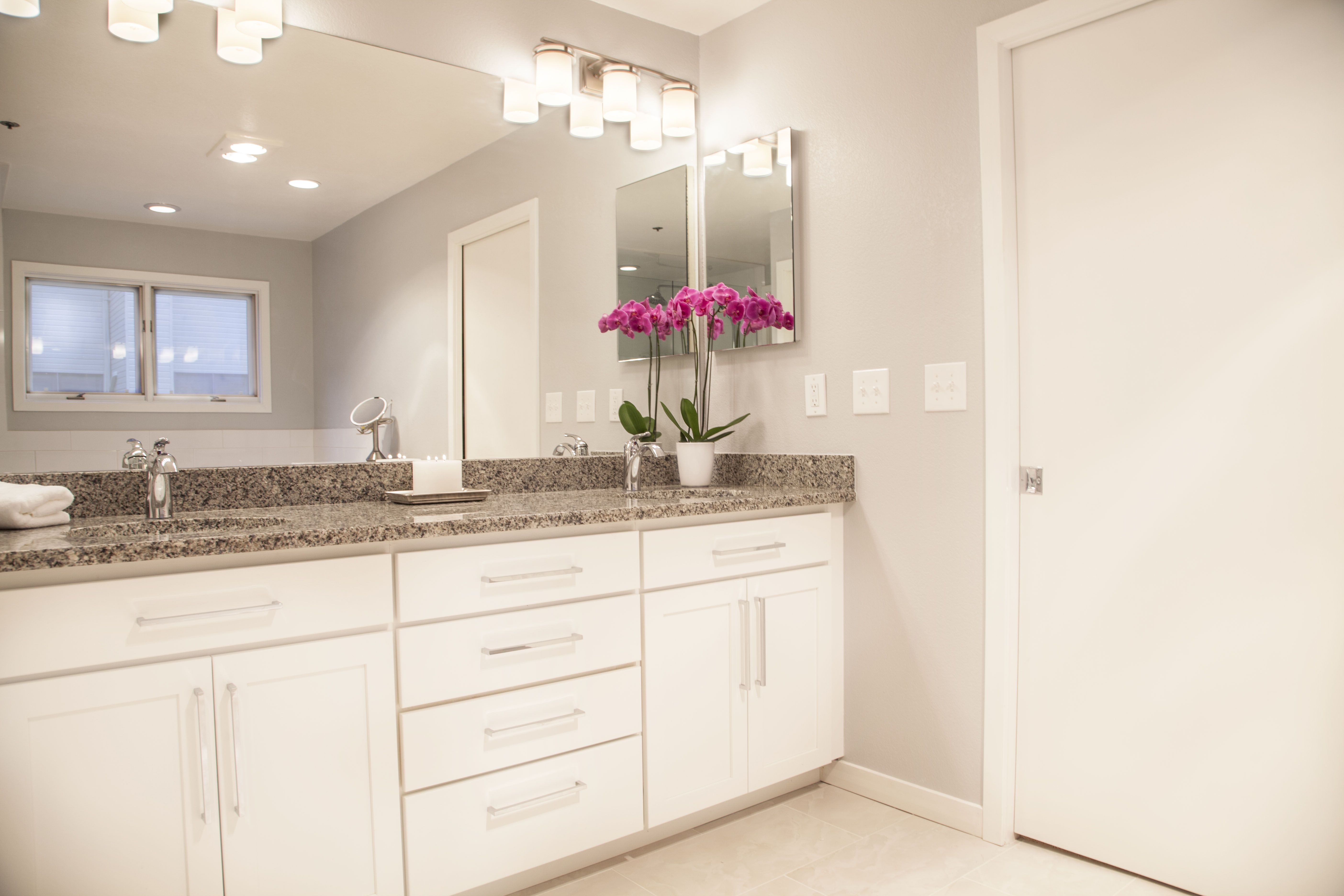 All white bathroom with gray granite and pop of color in the orchid. White cabinetry, white floors, white tile with polished chrome accents. Benjamin Moore Silver Linings on the wall. Wire handle pulls