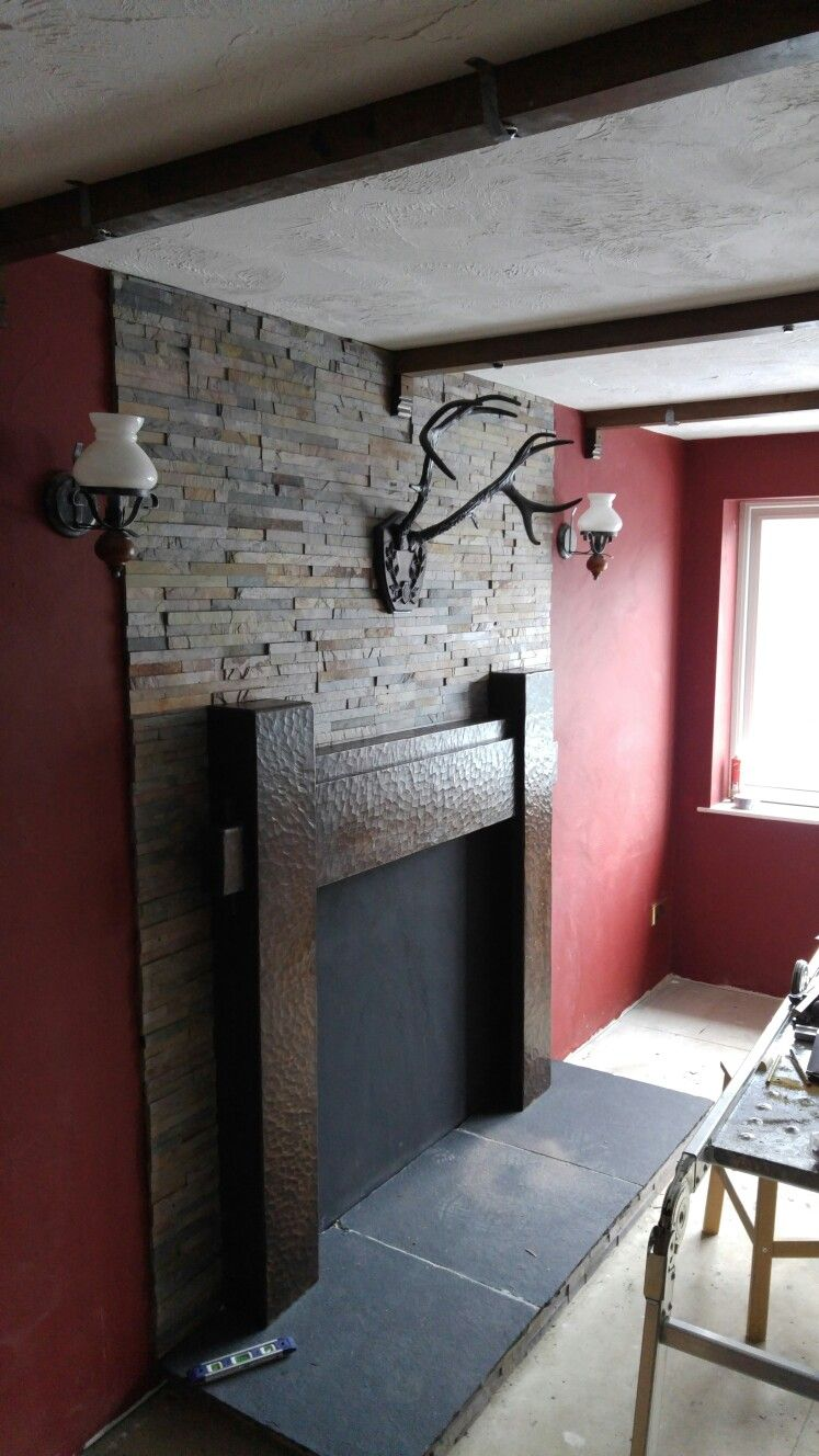 part-finished fireplace. Oak surround is c.1830, recovered from an old house demolished in Cheshire. Brass stag antlers and split slate to give illusion of a chimney breast