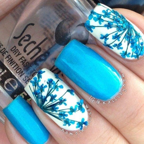 Lindas uñas en azul cielo y blanco adornadas con diseños florales en las uñas  blancas,
