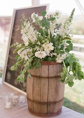 Small rustic wine barrels as flower decoration holders in wedding. Floral  Design: Fleur de