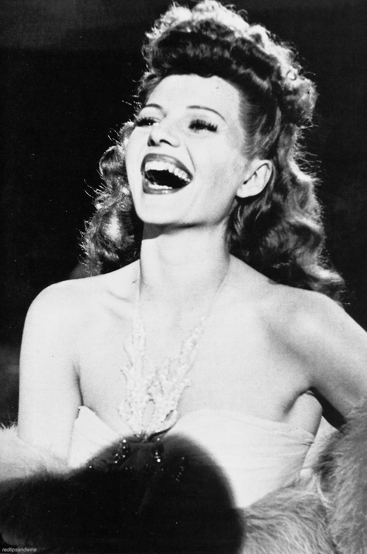 Rita laughs gaily on the set of Cover Girl (1944), a