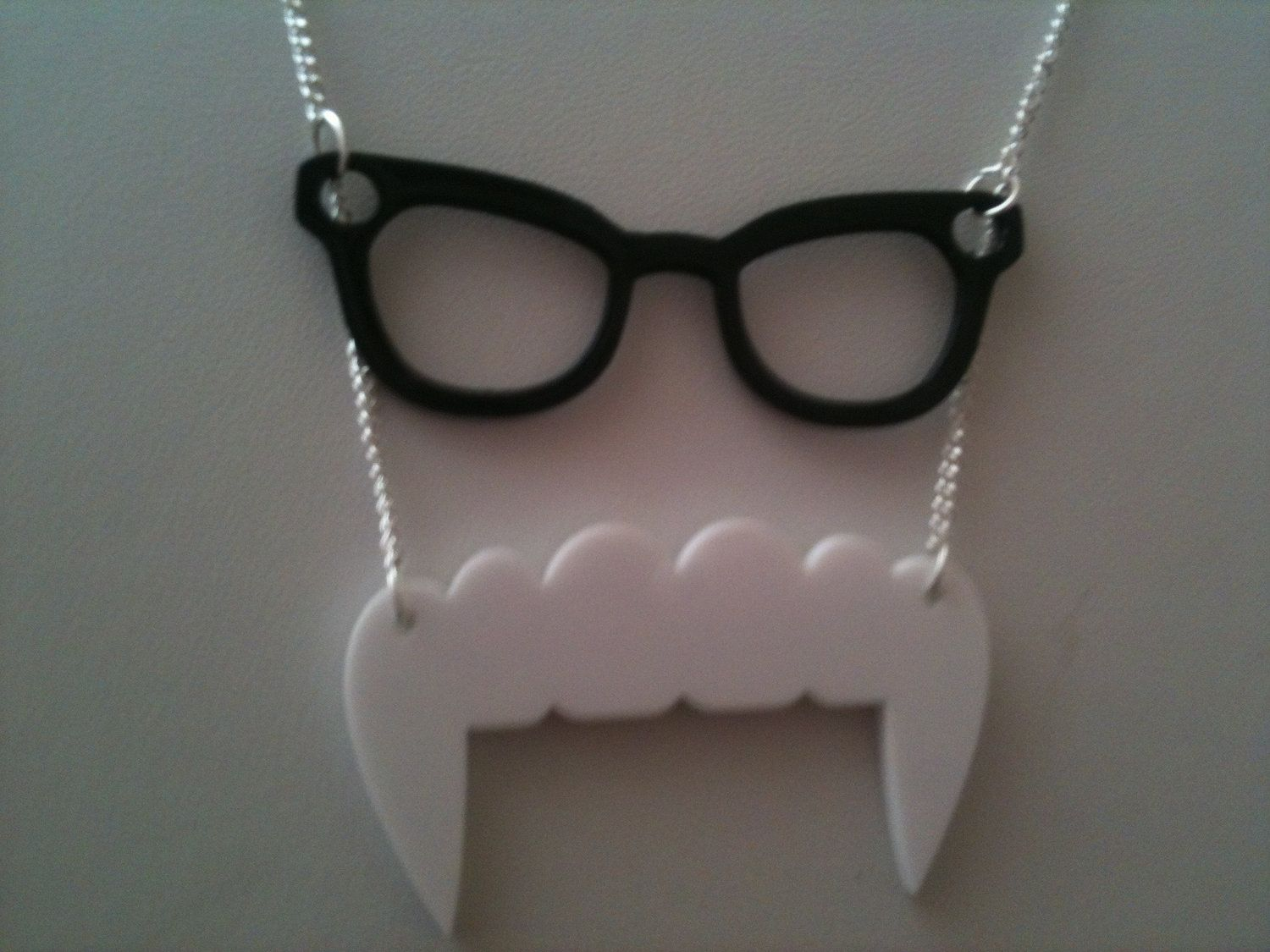 Vampire / nerd necklace on Etsy... vampire teeth with thick rimmed glasses... this is soo much fun