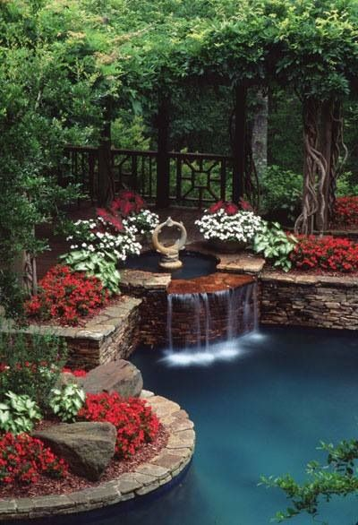 love the red flowers next to the water fall in this pool