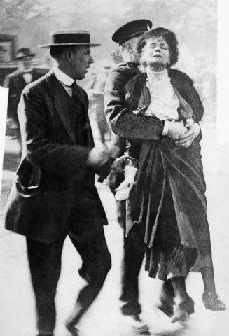 Emmeline Pankhurst is led away by a policeman after leading a group of suffragettes in an attempt to present a petition to the King at Buckingham Palace. 1 June 1914.