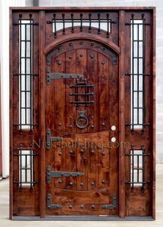 Rustic Exterior Arched Door With Wrought Iron Grills, Strap Hinges, Clavos  Nails And Door
