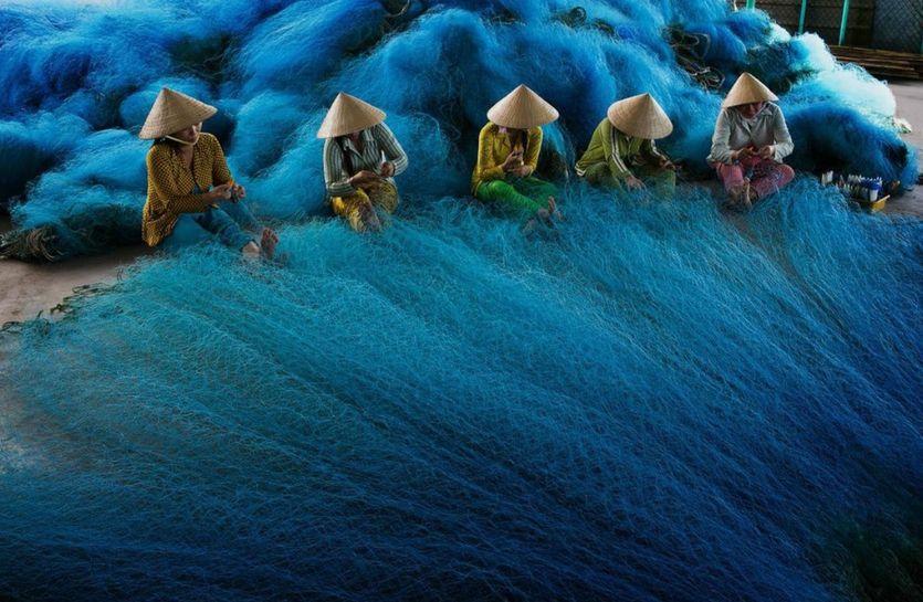 Esta es la foto que muestra  a un grupo de mujeres mientras tejen una azul de red de pesca en Vietnam. Se están preparando para  la inundación anual del río; momento en el que podrán pescar peces y camarón. Es de Tuyet Trinh Do, 2012. - See more at: http://culturacolectiva.com/el-concurso-que-premia-al-mejor-fotografo-ambiental/#sthash.UiOrdhxN.dpuf