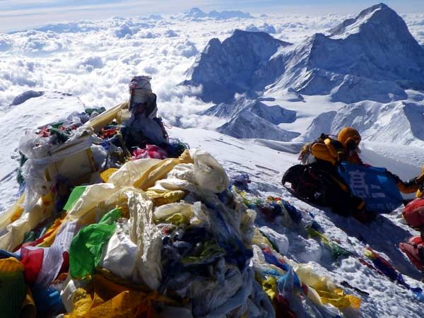 Everest's summit cairn bedecked in prayer flags, with Makalu in the
