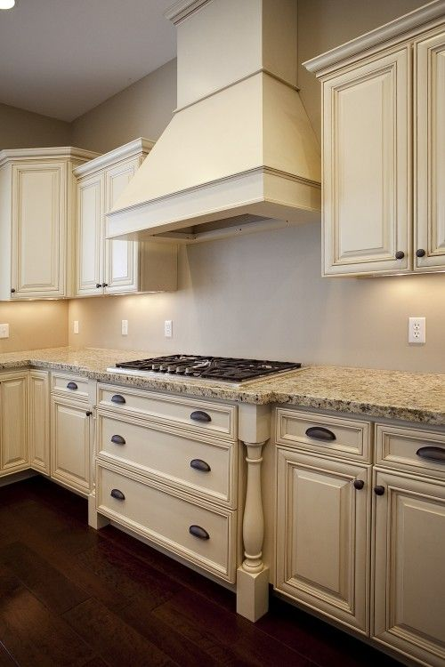 Love the antiqued cream cabinets and light countertop for Light colored kitchen cabinets