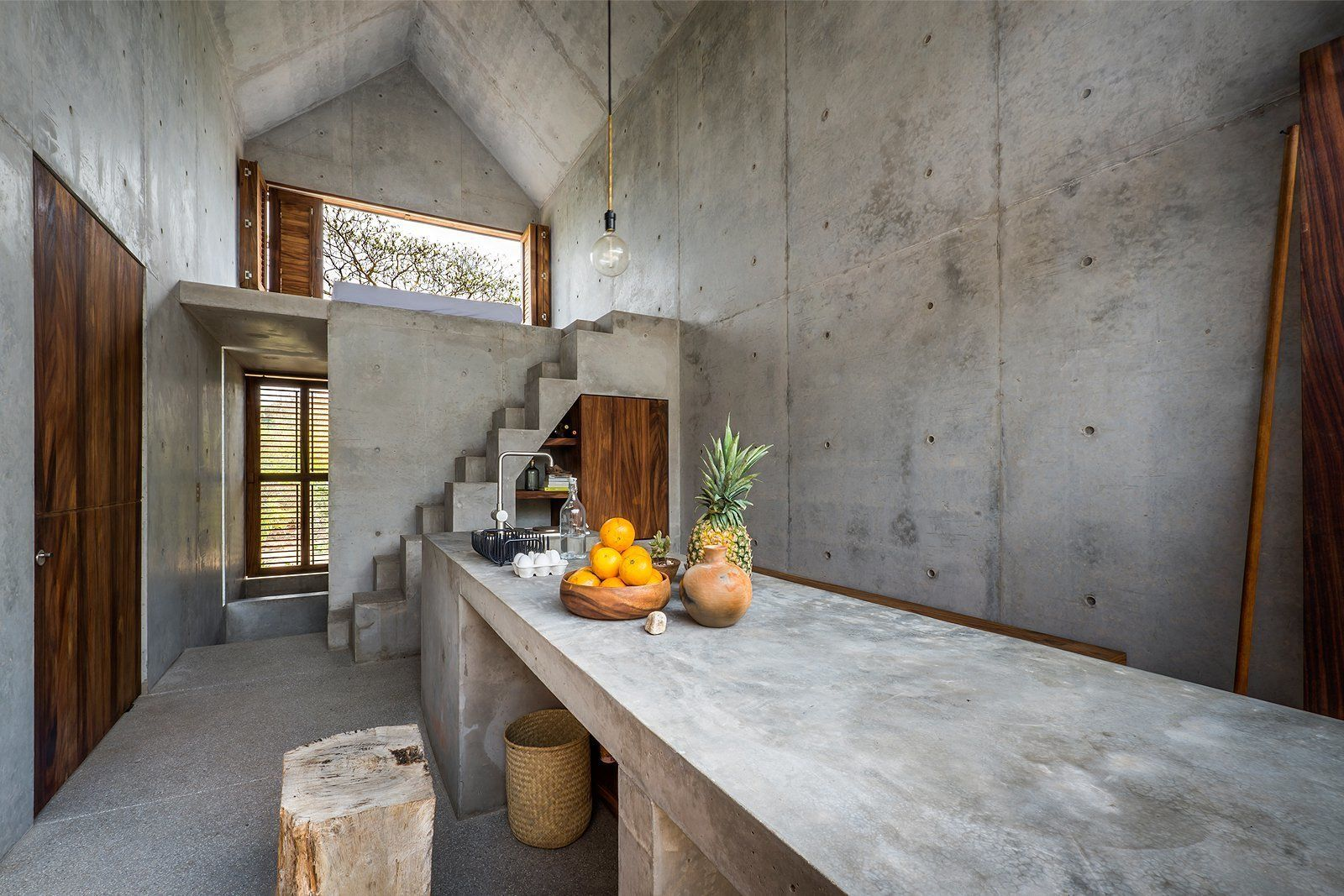 Pendant lighting concrete floor and drop in sink the concrete countertops walls and staircase echo the homes refined modern design aesthetic
