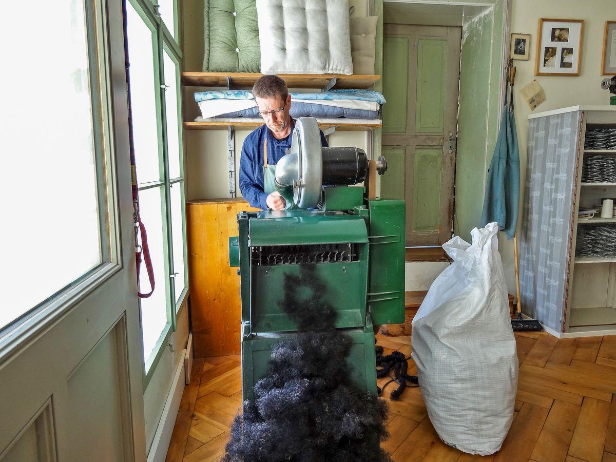 An der Zupfmaschine werden die gedrehten Rosshaarstränge aufgezwirbelt und so für die Füllung vorbereitet. Wird ein ganzer 13-kg-Sack aufgezupft, ist der gesamte Fussboden der Werkstatt mit Rosshaar bedeckt.