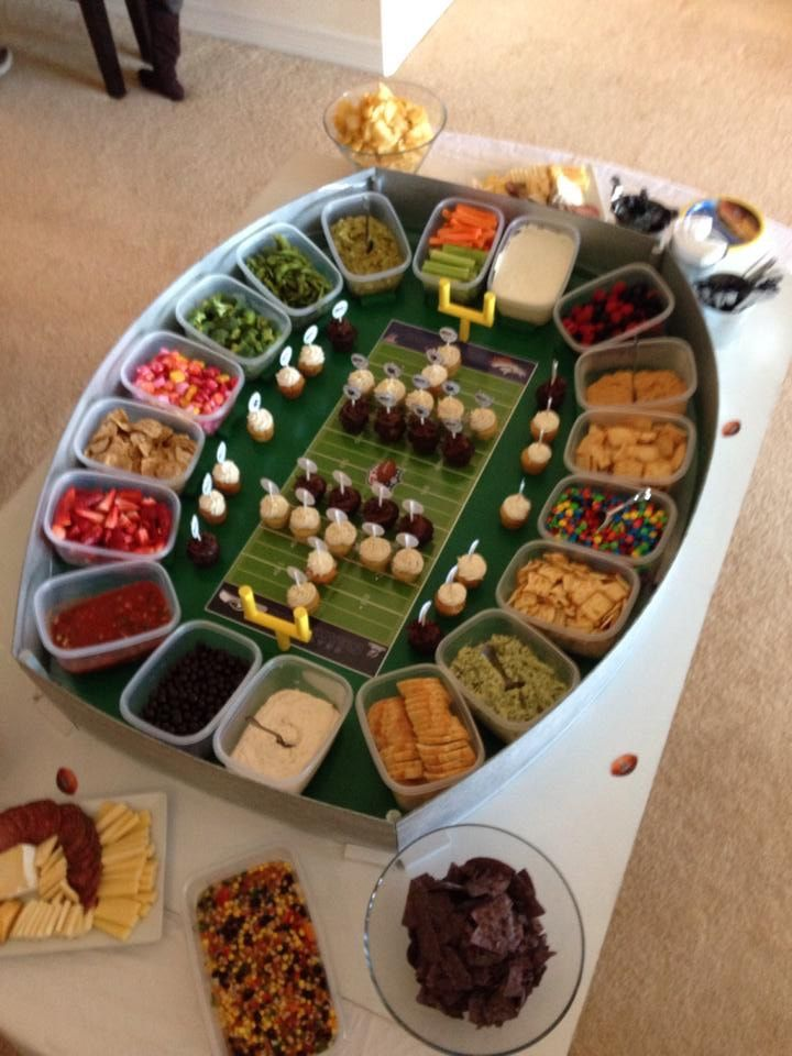 Snack Stadium, Super Bowl - When we set out to make a Snack Stadium, we wanted it to be clean and easy. The reusable containers helped us achieve this. We customized with a printed field that featured the two teams playing. Custom cupcake toppers on mini cupcakes served as the players. The field goals were created using wooden dowels painted yellow. The Snack Stadium was a huge success! Our guests loved the look and the clean up was so easy #footballfood