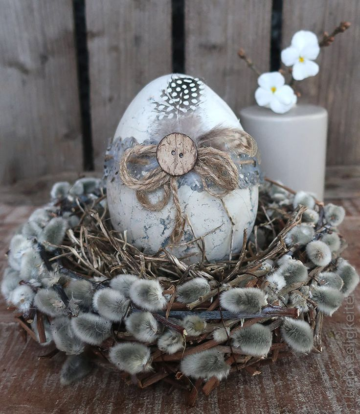 Photo of Easter decoration – a wreath of catkins with a large concrete egg