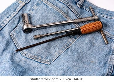 Working tools in jeans pocket. Close up. Top view. Repair concept. #1st of may, #background, #blue, #board, #card, #carpenter, #celebrate, #celebration, #closeup, #clothing, #concept, #construction, #day, #denim, #equipment, #fashion, #greeting, #hammer, #happy, #helmet, #holiday, #home, #industrial, #industry, #jeans, #label, #labor, #labour, #male, #material, #mechanic, #metal, #nail, #national, #nobody, #object, #old, #pliers, #poster, #remodeling, #repair, #steel, #tool, #top view, #vintage,