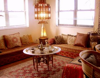 Traditional Moroccan living room with low benches and brass tray ...