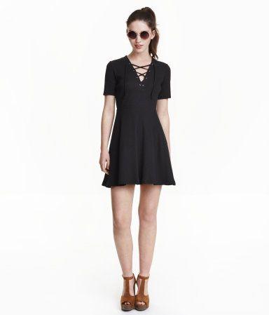 Kurzes Kleid aus geripptem Baumwolljersey. Das Kleid hat einen tiefen V-Ausschnitt mit Schnürung und kurze Ärmel. Taillennaht und Tellerrock. Ungefüttert.