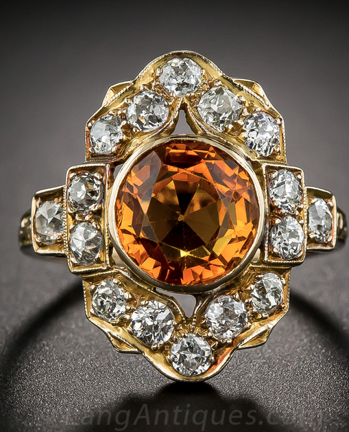 Antique Citrine and Diamond Dinner Ring  A blast of bright orange sunshine, in the form of a round faceted golden citrine, radiates from the center of a dazzling diamond dinner (or right hand) ring dating back to the first decade of the last century. 16 old mine-cut diamonds, totaling 1 carat, are arrayed over a curvaceous 14K gold frame and shoulders finished with artful hand engraving on the upper ring shank.