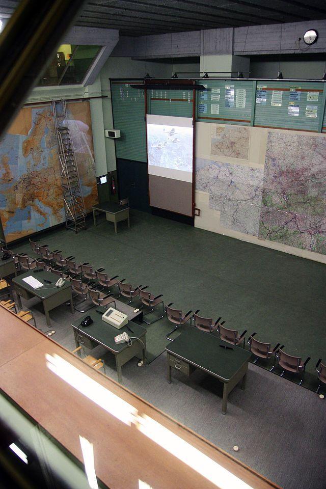 Operationsroom - Commandobunker van Kemmel - In 1953, zo'n acht jaar na het einde van de Tweede Wereldoorlog, werd in de Kemmelberg in Kemmel (België) een gigantische put gegraven. Over de bouw van de oorlogsbunker herinneren oudere streekbewoners zich nog dat er honderden vrachtwagens aarde werd weggevoerd door vreemde arbeiders, die geregeld gewisseld werden. Men wist alleen dat het leger hier tussen 1952 en 1956 een ondergrondse bunker bouwde. De ware toedracht bleef een groot mysterie.