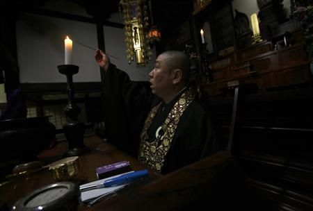 Japan priest fights invisible demon: radiation | Reuters  Koyu Abe, a Zen priest, lights a candle at the main hall of his Joenji temple in Fukushima, northern Japan February 3, 2012.  REUTERS/Yuriko Nakao