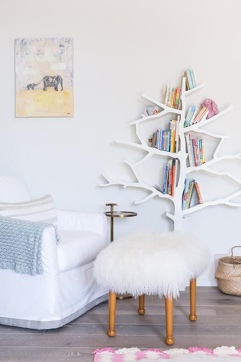 Beautifully Ointed Nursery Boasts A White Slipcovered Glider Positioned Facing Sheepskin Stool Placed In Front Of Works Tree Bookcase Fixed