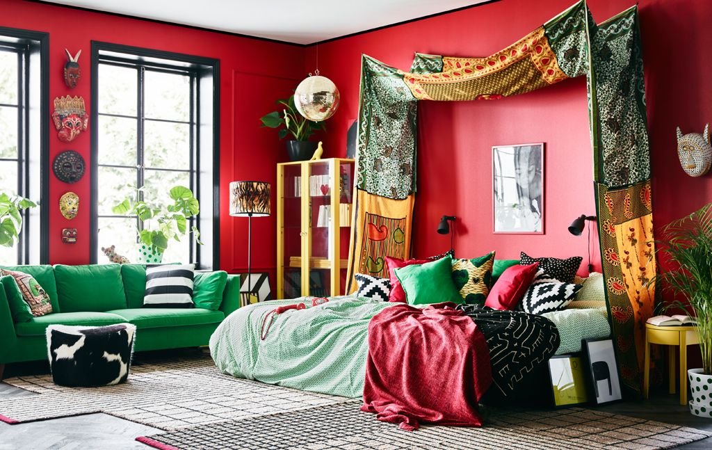 Bright textiles, colourful furniture and red walls help give this bedroom its distinctive look.
