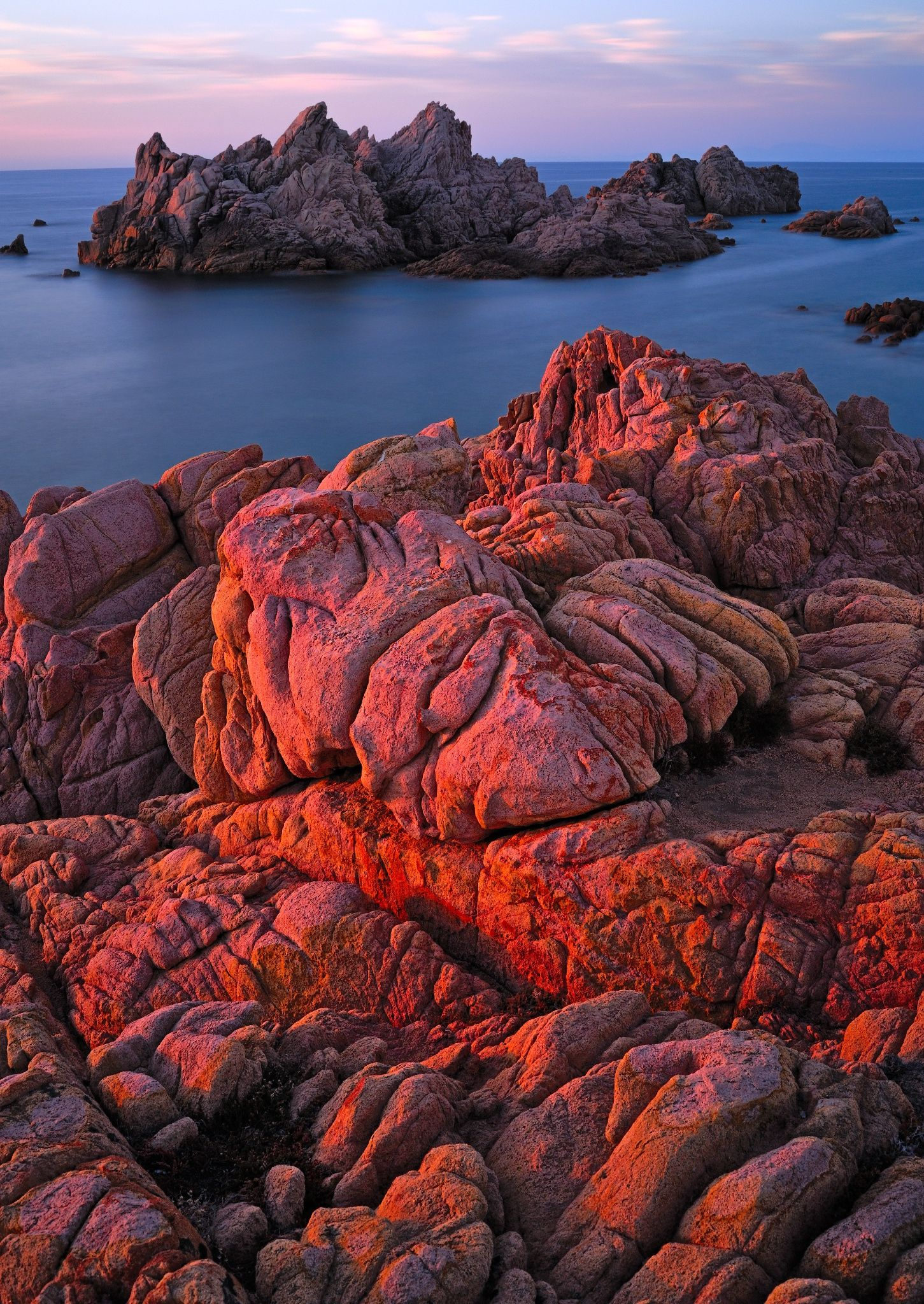 Sunset's warm light fires up the rocks in Cala Rossa.