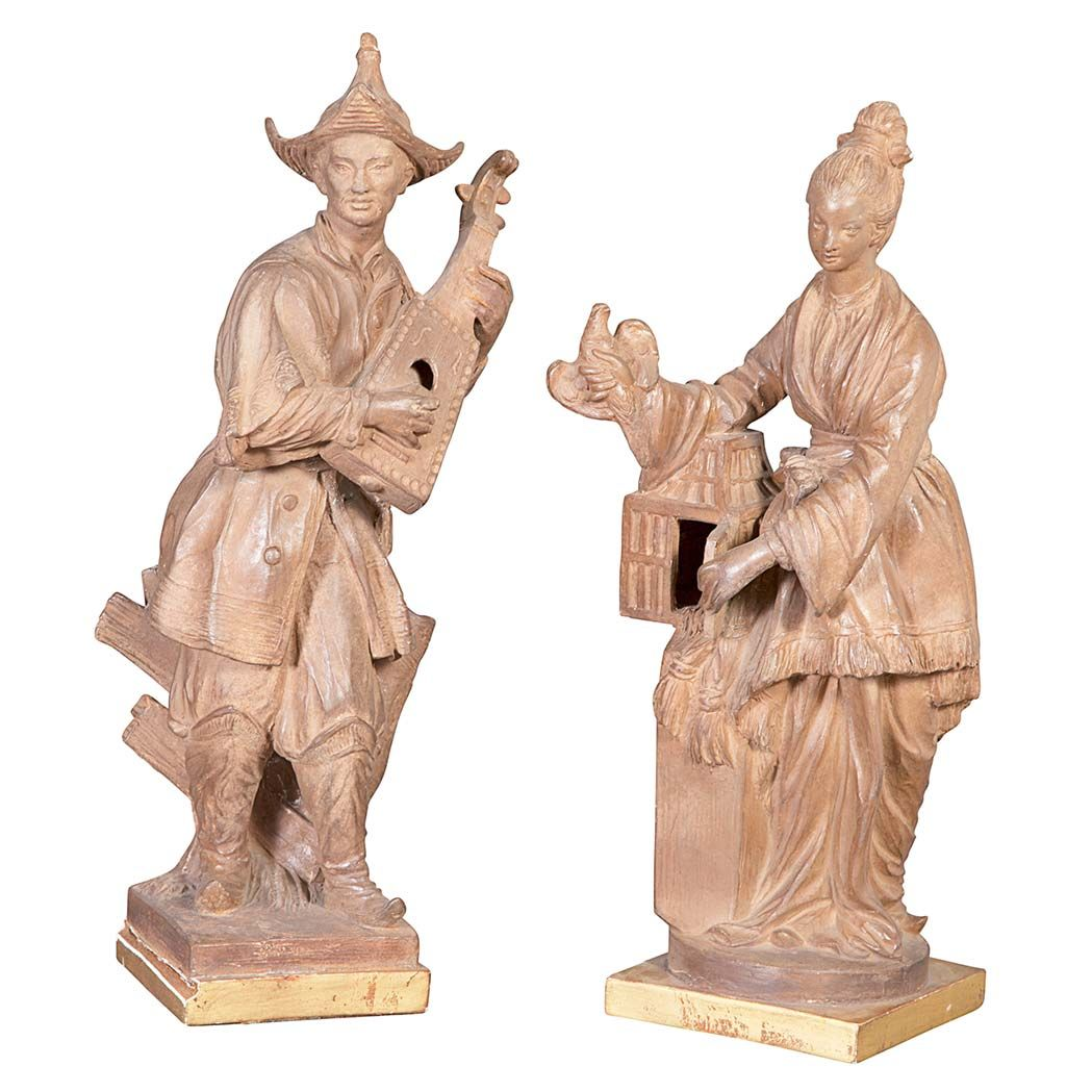 Pair of Continental Terra Cotta Figures  Each in chinoiserie dress, the man with a lute and the female with a bird cage.