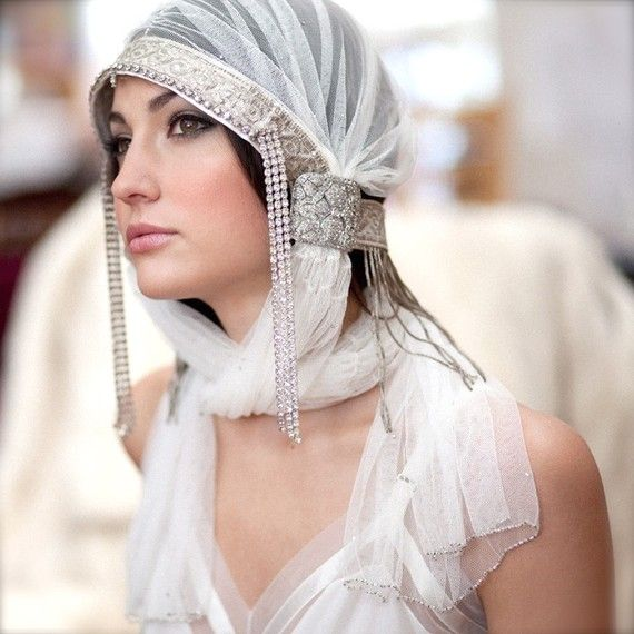 """A princess bride in soft snow white. Melt hearts in this exquisite art deco inspired veiled headdress. Veils are 26"""" in length and hand beaded along the bottom edge with silver lined glass seed beads and Victorian cut steel beads. The frame is built over milliners wire to support the fluid tulle and frame the face."""