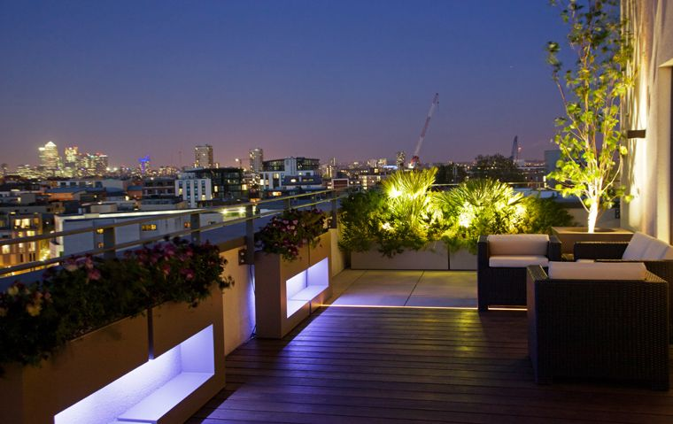 Bermondsey roof terrace with view of Canary Wharf at night time