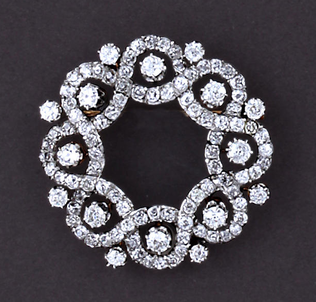 A belle époque diamond brooch, circa 1910, French  of openwork and circular outline, set throughout with old mine and old European-cut diamonds in a braided motif; with French assay marks; estimated total diamond weight: 6.25 carats; mounted in platinum topped eighteen karat gold