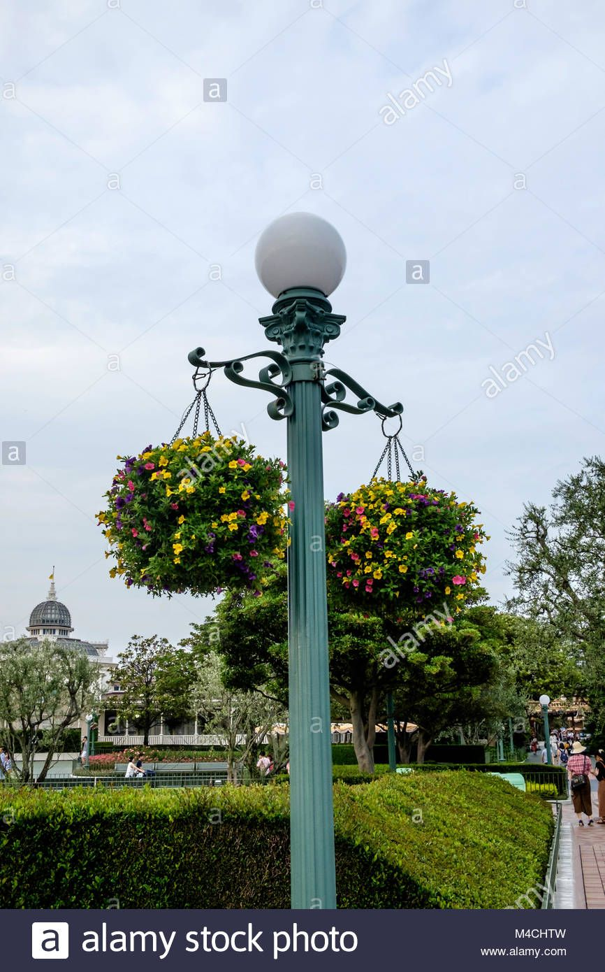 Ornate Metal Lamp Post With Round Globe Light On Top With Two Baskets Full Of Flowers Hanging On Either Side Disneyland Tok Lamp Post Metal Lamp Globe Lights