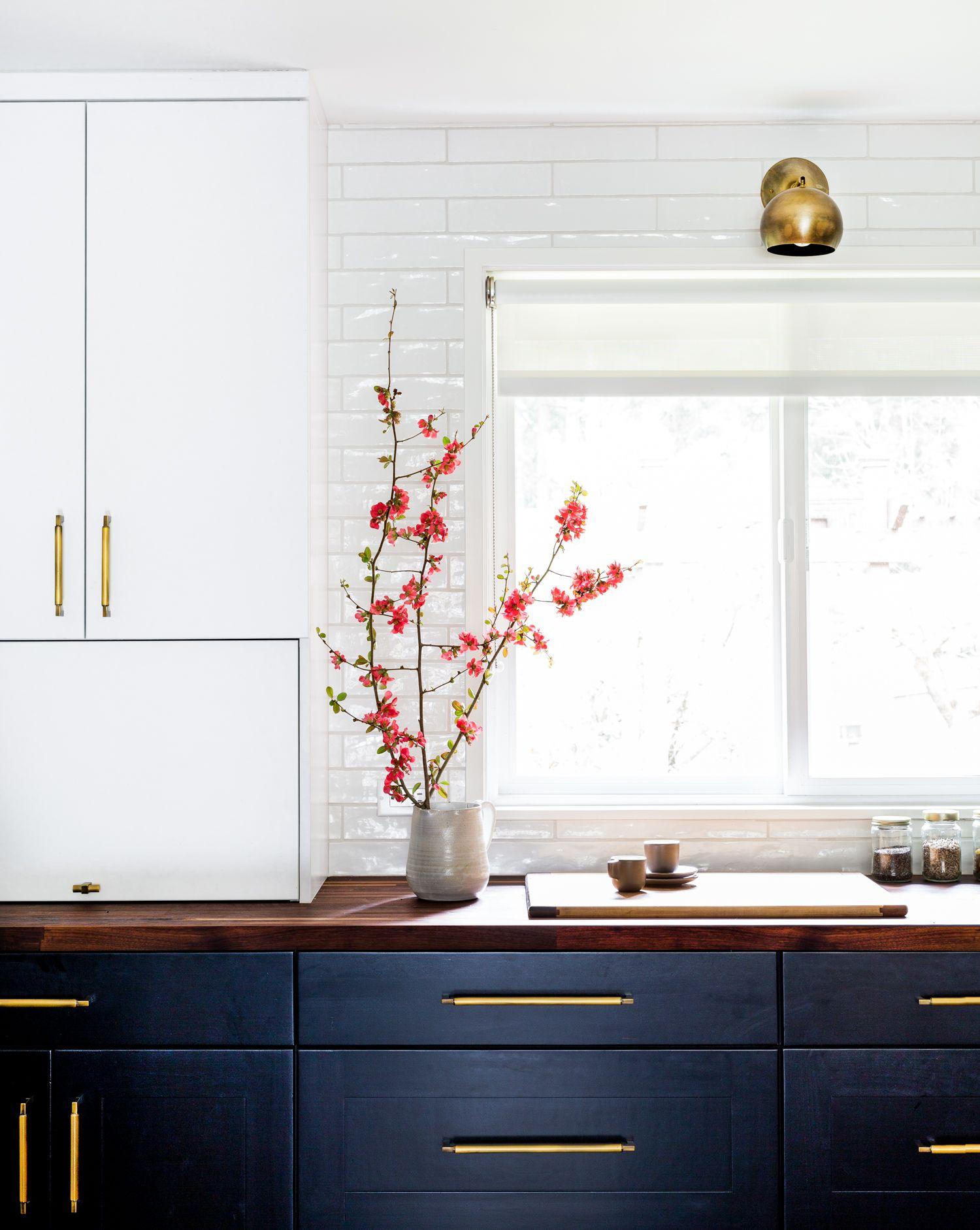 Dark lower cabinets, brass hardware, butcher block countertops ...